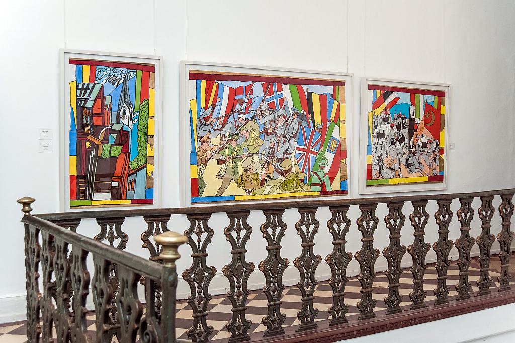 Blick auf die Ausstellung. Drei Gemälde im Hintergrund, im Vordergrund ein Geländer