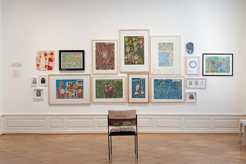 Bilder der Ausstellung an der Wand. Davor ein unbesetzter Stuhl.